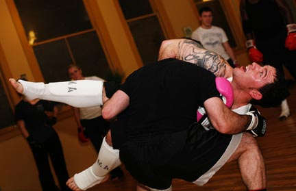Seth MacDonald is picked up during a demonstration by teacher Rob Eis on how to defend against the guillotine choke hold.