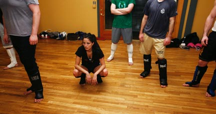 Felicia Molano watches as her mixed martial arts teacher explains the next move they will practice at the Unbridled Martial Arts studio.