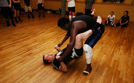 Unbridled Martial Arts studio instructor, Rob Eis, left, with the aid of his student, Manis Pierre, explains how to avoid getting slammed against the floor by a larger opponent.
